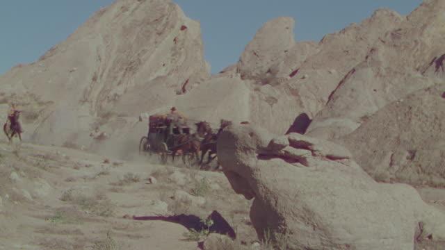 vidéos et rushes de ws pan shot of cowboys on horseback chasing horse and buggy speeding through desert  - voiture hippomobile