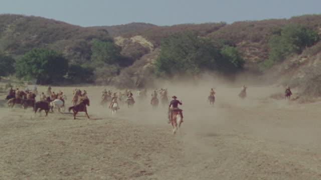 ws shot of cowboys on horseback speeding in desert area - espansione verso l'ovest video stock e b–roll