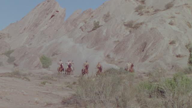 ws ts pan shot of cowboys running on horseback in desert - espansione verso l'ovest video stock e b–roll