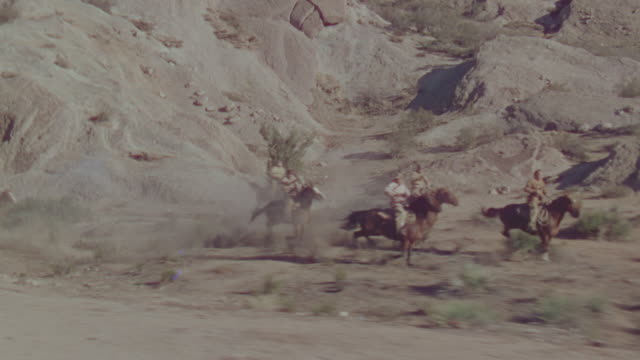 MS POV TS Shot of cowboys running on horseback through desert