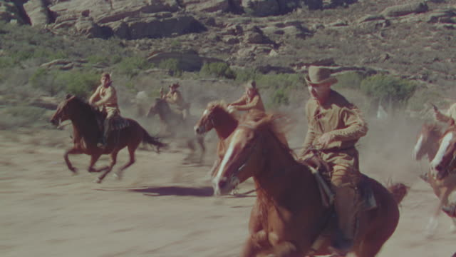 ms pov shot of cowboys running on horseback - カウボーイ点の映像素材/bロール