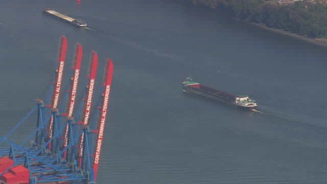 ms aerial shot of cranes with moving boat in hamburg port / germany - western script stock videos & royalty-free footage