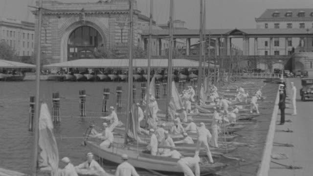 vidéos et rushes de ms shot of crew of sailors on dock preparing to launching their sail boats  - marinière