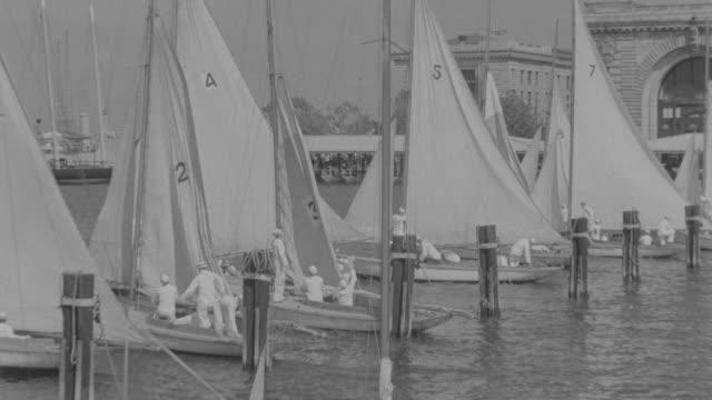 vidéos et rushes de ms pan shot of crew of sailors on dock preparing to launching their sail boats  - marinière
