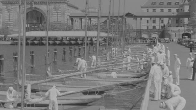 vidéos et rushes de ms shot of crew of sailors on docks preparing sail boats for launch - marinière