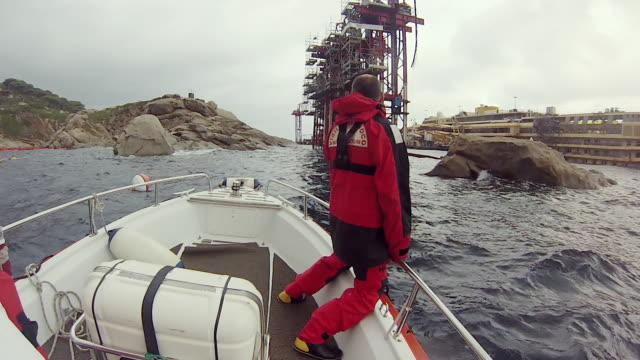 ms pov shot of crew on boat arrives at site of now upright costa concordia / giglio porto, tuscany, italy - sink stock videos and b-roll footage