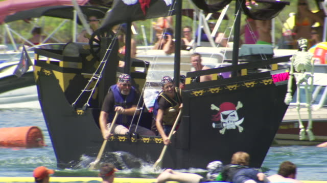 WS TS Shot of crew paddling pirate boat during World Championship Cardboard Boat Race / Heber Springs, Arkansas, United States