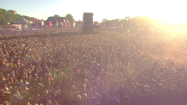 cu pov zo shot of crowd going wild hands up in air with sunrise  / victoria park, london, united kingdom - コンサート点の映像素材/bロール