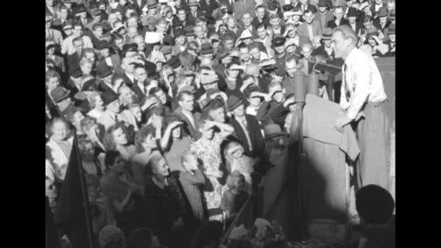 shot of crowd / two shots of communist party of germany leader max reimann speaking to crowd / election results posted on wall / reimann leaving... - ヘッセン州点の映像素材/bロール