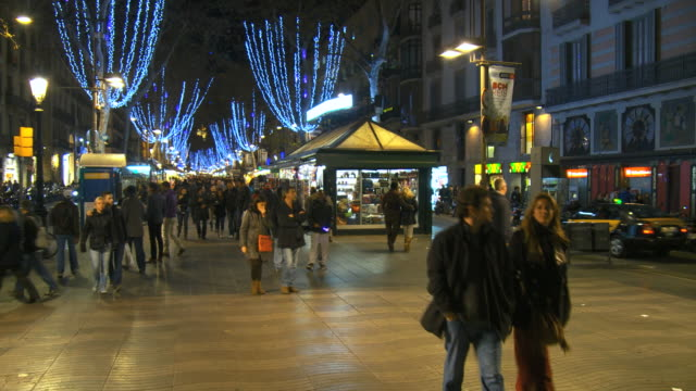 ms pan shot of crowd walking on street in la rambla with christmas lights and decorations illuminated at night / barcelona, catalonia, spain - 飾りつけ点の映像素材/bロール