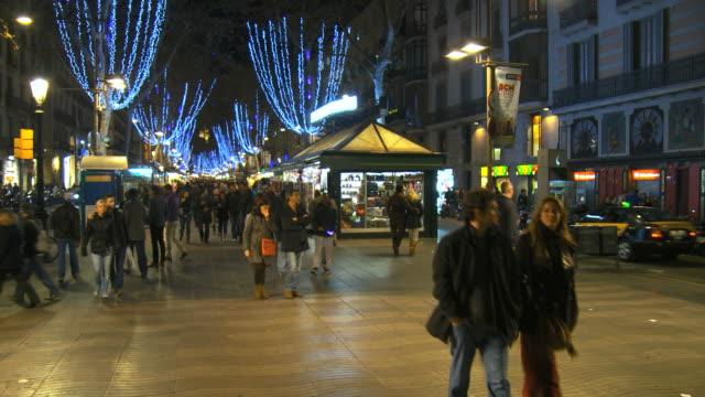 vídeos y material grabado en eventos de stock de ms pan shot of crowd walking on street in la rambla with christmas lights and decorations illuminated at night / barcelona, catalonia, spain - cultura mediterránea