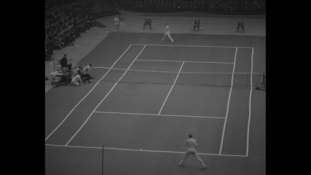Shot of crowd watching match at Madison Square Garden / long volley between Frank Kovacs and Don Budge / crowd applauding / Kovacs serving / long...