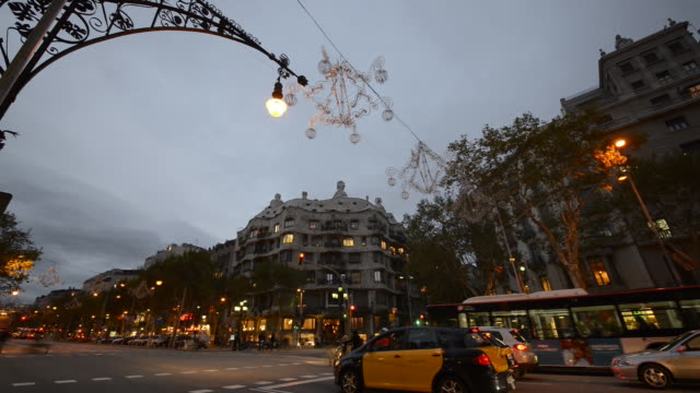 MS T/L Shot of crowded area of Passeig de Gracia and Casa Mila at dusk / Barcelona, Catalunya, Spain
