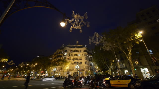 MS Shot of crowded area of Passeig de Gracia and Casa Mila at dusk / Barcelona, Catalunya, Spain
