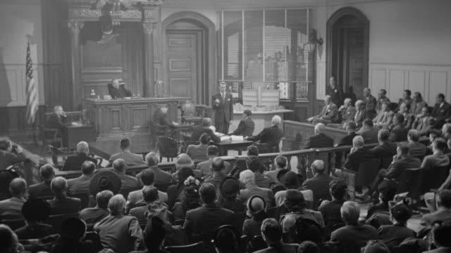 vídeos y material grabado en eventos de stock de ms shot of crowded courtroom viewed from rear looking toward judge - abogado
