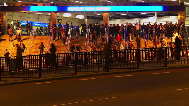 MS T/L Shot of Crowds leaving Wembley Park station at night / London, United Kingdom