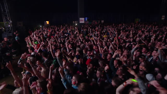 MS POV Shot of Crowds rocking out hands up in air with white light flashing across occasionally / Isle of Wight, London, United Kingdom