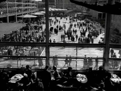 shot of crowds walking along a concourse taken from inside the restaurant at the festival of britain 1951 - festival of britain stock videos & royalty-free footage