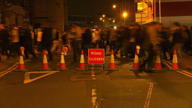 "MS T/L Shot of Crowds walking past ""Road Closed"" sign at night / London, United Kingdom"