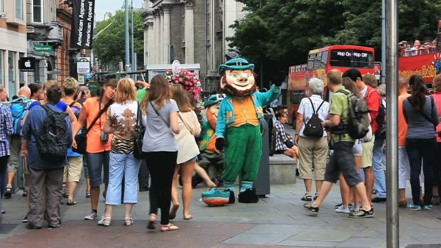 MS Shot of Crowds watching Street performance with Leprechaun costume at Grafton Street / Dublin, Dublin Region, Ireland