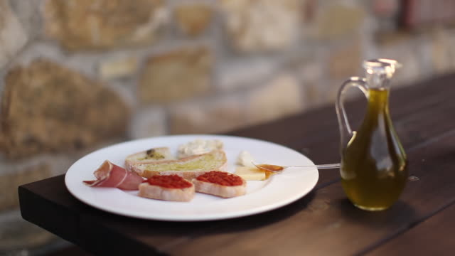 cu r/f shot of cruet of extra virgin olive oil to dish of bruschettas / castellina in chianti, tuscany, italy - olive oil stock videos & royalty-free footage