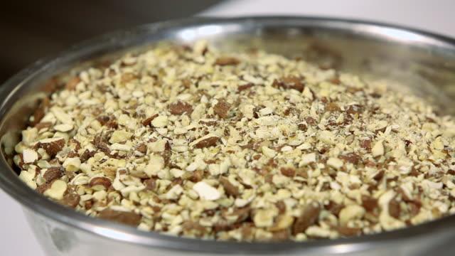 cu r/f shot of crushed almonds in bowl / rome, lazio, italy - アーモンド点の映像素材/bロール