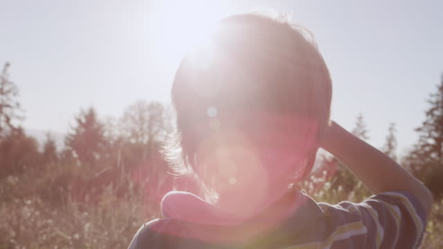 CU SLO MO Shot of curious young boy scans thetreeline as sun flares dramatically / Beaverton, Oregon, United States