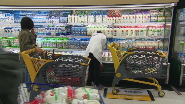 shot of customer looking at milks in supermarket. - dairy product stock videos & royalty-free footage