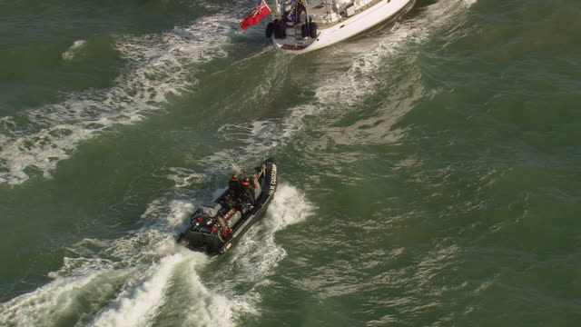ws aerial zi zo shot of customs patrol craft and rescue boat moving ahead in sea / suffolk, france - police boat stock videos and b-roll footage