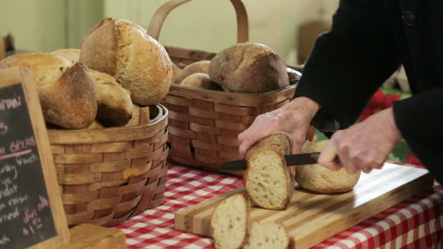 MS Shot of Cutting bread for samples in Vermont farmers market / Rutland, Vermont, United States