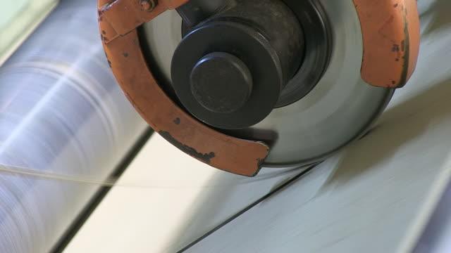 CU Shot of cutting paper by machine in paper mill / Gmund, Bavaria, Germany