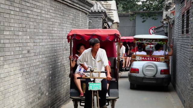 ms shot of cycle rickshaw drivers taking tourists in alley at houhai lakes area / beijing, china - rickshaw stock videos and b-roll footage