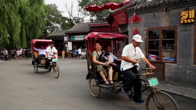 ms shot of cycle rickshaw drivers taking tourists on tour ofhouhai lakes area / beijing, china - risciò video stock e b–roll