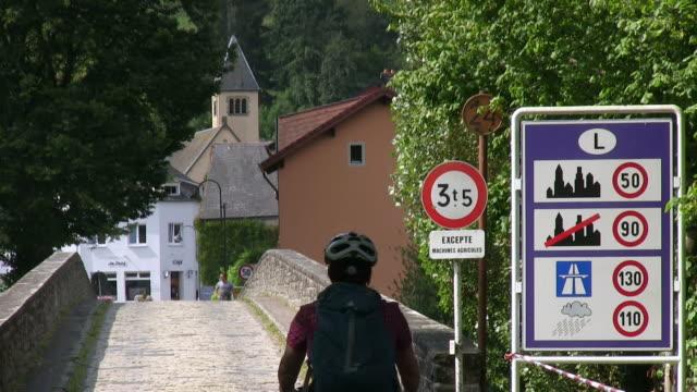 vidéos et rushes de ms shot of cyclist at old sauer bridge / dillingen, echternach, luxembourg - signalisation routière