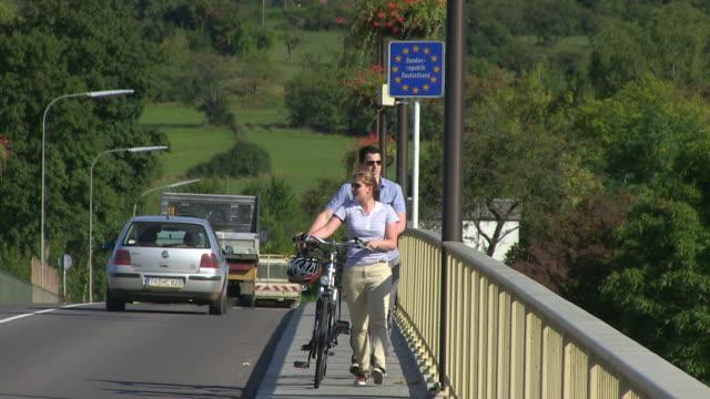 vidéos et rushes de ms shot of cyclists at border bridge luxembourg-germany / schengen, moselle, luxembourg - grand duché du luxembourg