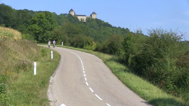 ms shot of cyclists near chateau marlbrouck / manderen, lorraine, france - lorraine stock-videos und b-roll-filmmaterial