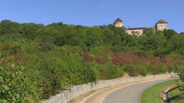 ms td shot of cyclists near chateau marlbrouck / manderen, lorraine, france - lorraine stock-videos und b-roll-filmmaterial