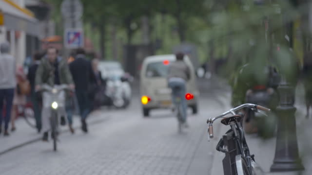 vidéos et rushes de shot of cyclists riding down a cobbled street in paris, france - mise au point au 1er plan
