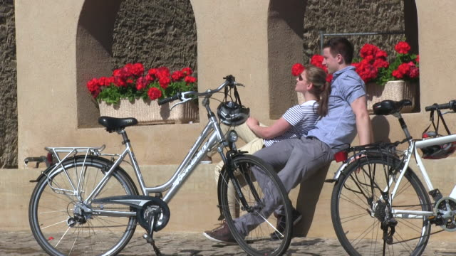 cu shot of cyclists sitting at old town / rodemack, lorraine, france - lorraine stock-videos und b-roll-filmmaterial