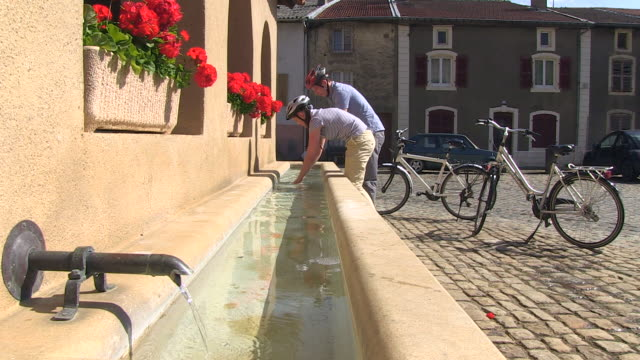 ms zi shot of cyclists washing hands at old town / rodemack, lorraine, france - lorraine stock videos & royalty-free footage