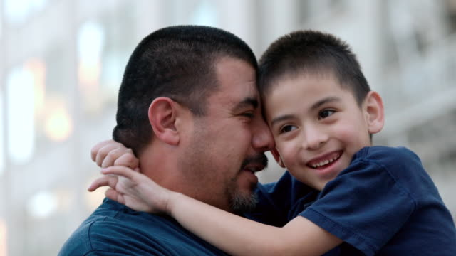 cu shot of dad holding his eight year old son are laughing and smiling genuinely / los angeles, california, united states - etnia latino americana video stock e b–roll