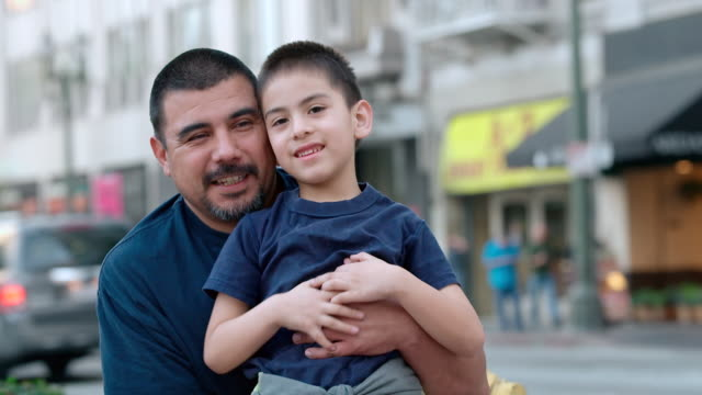 ms shot of dad kneeling to his eight year old son, smiling genuinely / los angeles, california, united states - etnia latino americana video stock e b–roll