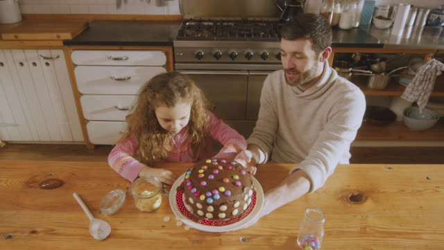 MS HA Shot of Daddy and daughter adding sweets as decoration to cake / London, United Kingdom