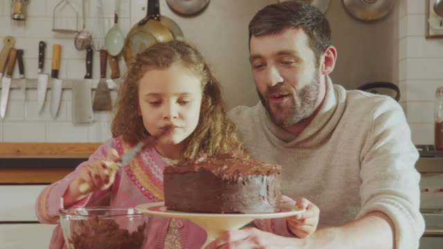 cu shot of daddy and daughter sitting at kitchen table adding chocolate icing to cake / london, united kingdom  - baking stock videos & royalty-free footage