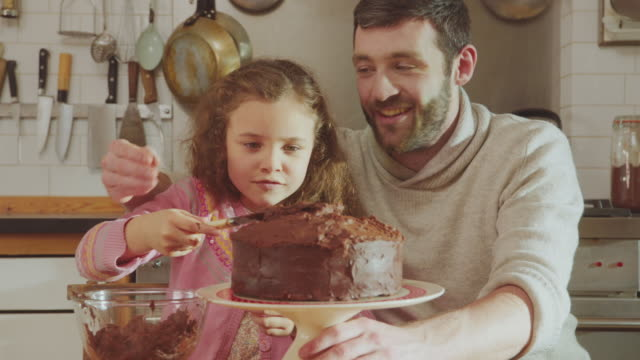 cu tu shot of daddy and daughter sitting at kitchen table adding chocolate icing to cake / london, united kingdom  - baking stock videos & royalty-free footage