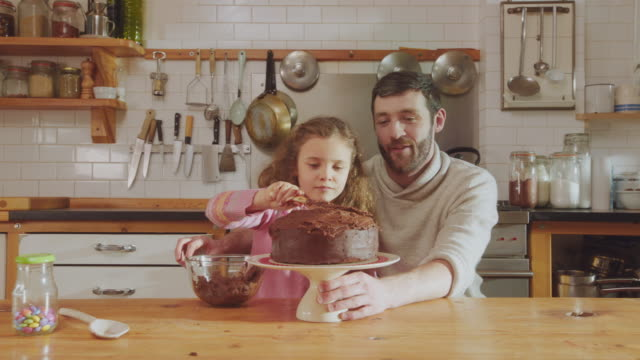 MS Shot of Daddy and daughter sitting at kitchen table adding chocolate icing to cake / London, United Kingdom