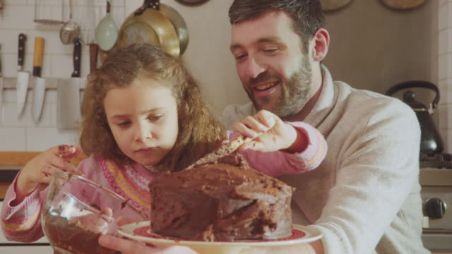 CU Shot of Daddy and daughter sitting at kitchen table adding chocolate icing to cake / London, United Kingdom