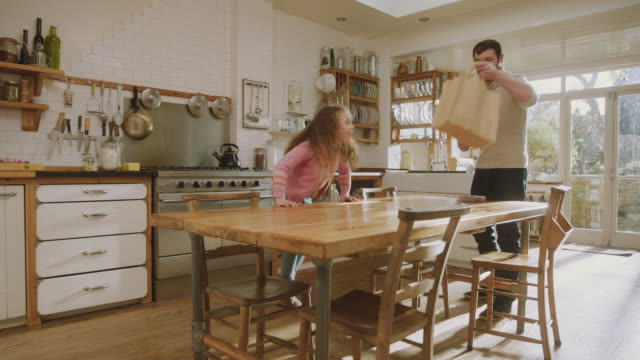 vidéos et rushes de ms shot of daddy & daughter get ingredients ready in kitchen then high fine / london, united kingdom  - bois