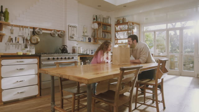 ms shot of daddy & daughter in kitchen discuss recipe, girl jumping with excitement / london, united kingdom  - father stock videos & royalty-free footage