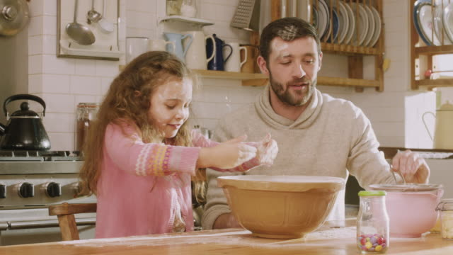 cu shot of daddy & daughter making mess while sieving flour in kitchen / london, united kingdom  - unordentlich stock-videos und b-roll-filmmaterial